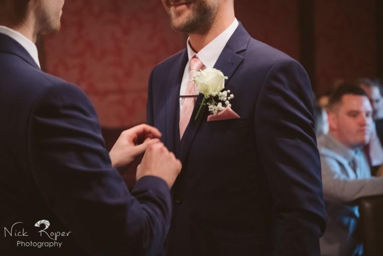 Best Man fixing the groom's flower