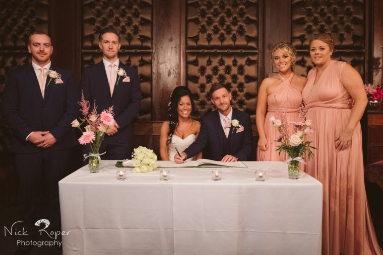 Bride and Groom signing register with witnesses standing either side