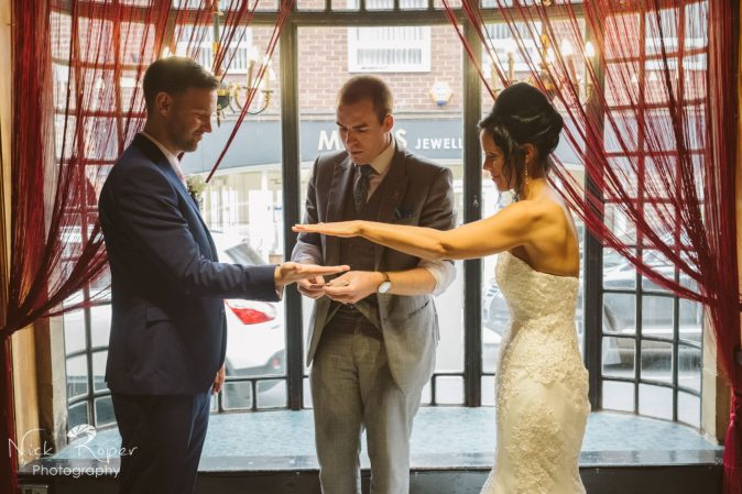Magician doing a card trick with bride and groom