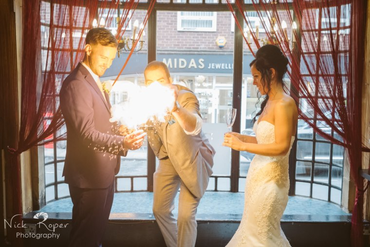 Magician creating big flash with bride and groom