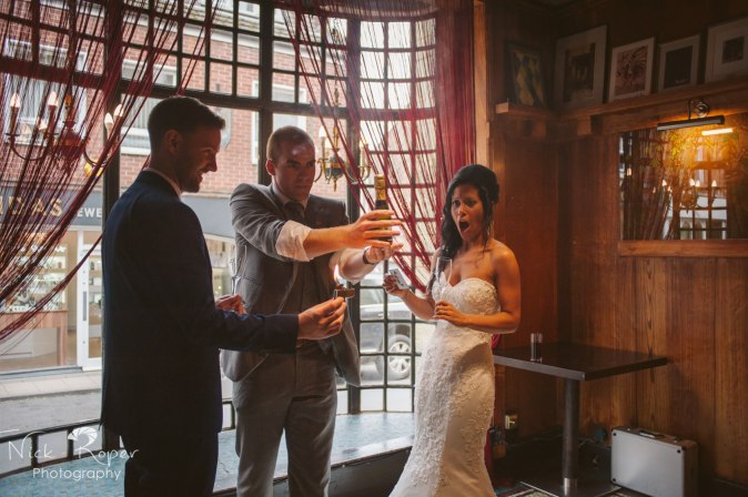 Magician creating bottle of champagne with bride looking shocked