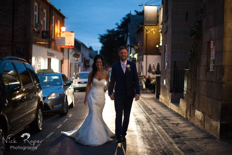 Portrait of Bride and groom walking in the middle of the road, backlit by headlights