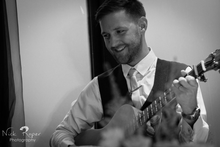 Groom singing and playing guitar to Bride